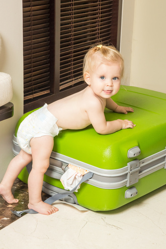 Cheerful baby leaning on the green travel luggage, indoor port